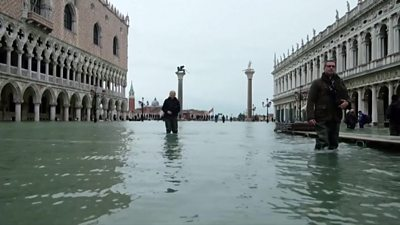 People walking through Venice floods