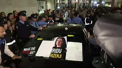 Protesters surround a car