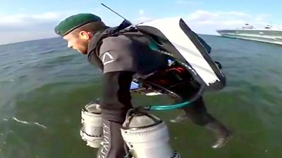 A man wearing a jet suit flying above open water