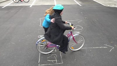 A woman being helped to ride a bike