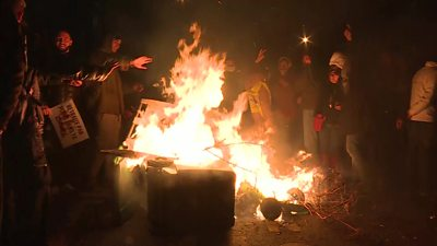 Protesters start a fire on the roadside
