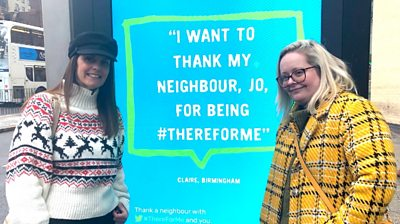 Jo Stretch and Claire Johnson next to the billboard