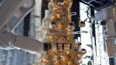 A robot decorates a Christmas tree