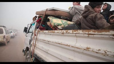 Family travel in a truck heading north away from air strikes in Idlib province, Syria