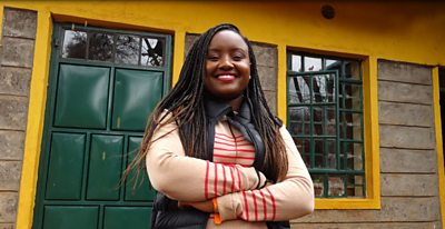 Waira Njiru smiles in front of a school building