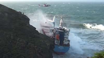 A crew member is winched to safety from a cargo ship off the coast of Sardinia