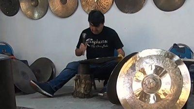 Man hammering a cymbal in workshop