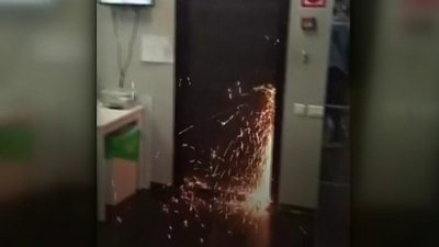 Sparks fly as officers cut open the door of the anti-corruption foundation
