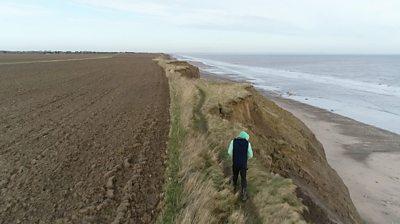 Man walking along the cliff edge