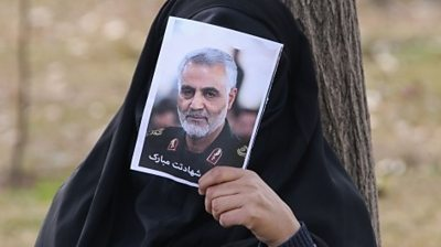 woman covers face with photo of Soleimani, Tehran