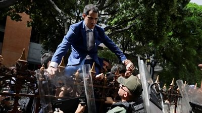 Venezuelan opposition leader Juan Guaido climbs a fence in an attempt to enter the headquarters of the National Assembly