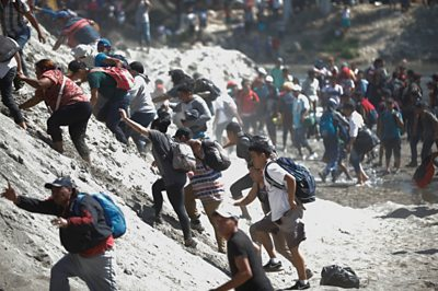 Migrants cross a river between Guatemala and Mexico