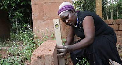 Jane Ifeoma measuring a brick