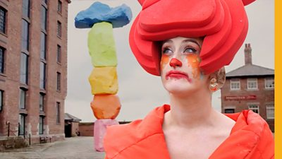 A woman dressed as a clown stands in front of Tate Liverpool staring into the distance