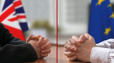 Two men's hands across a negotiating table, in front of UK and EU flags