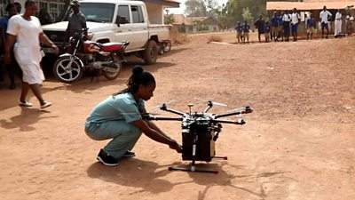 A nurse takes medical supplies from a drone