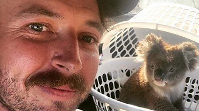 Man's face in foreground and koala in background