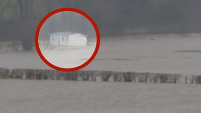 A caravan highlighted floating in flood water