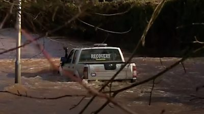 4 x 4 truck with 'recovery' markings in rear windscreen floats on flooded road