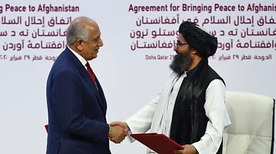 Zalmay Khalilzad and Taliban co-founder Mullah Abdul Ghani Baradar shake hands