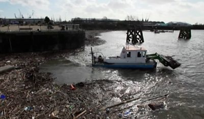 A boat cleaning debris out of the River Taff