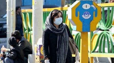 A woman wearing a face mask walking on a street in Iran