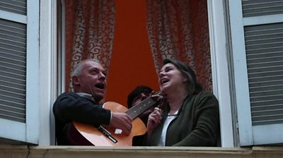 Man and woman singing at window