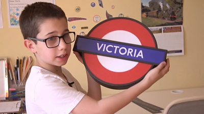 Isaac holds a replica Underground station sign