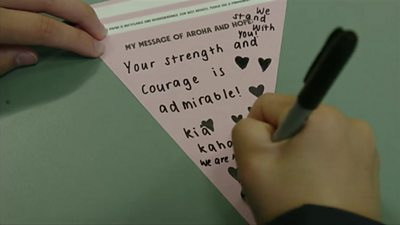 A child writing a banner that says 'your strength and courage is admirable'