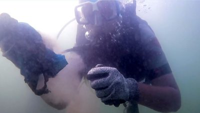 A scuba diver cleaning the ocean