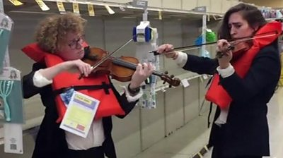 Two women playing violin in supermarket wearing lifejackets