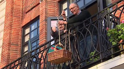 Suzi and David Ashcroft raising a basket to their balcony