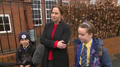 Mother and children outside school gates