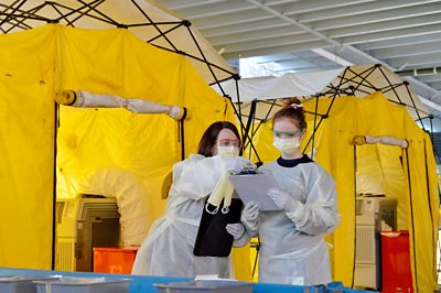 Two nurses test people for the virus in a makeshift drive thru clinic.