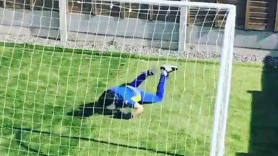 A child diving in goal