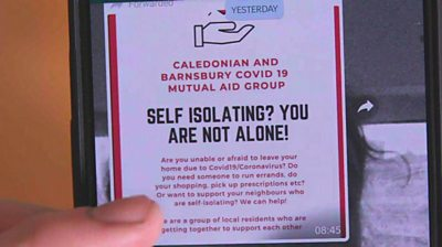 A volunteer group to help people self-isolating shown a mobile phone