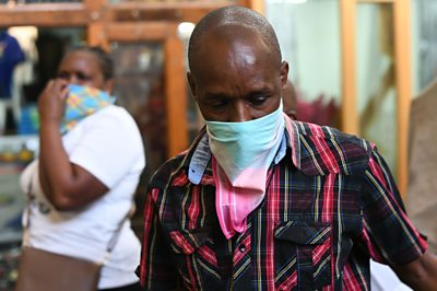 A curio trader covers his nose at the market in Nairobi