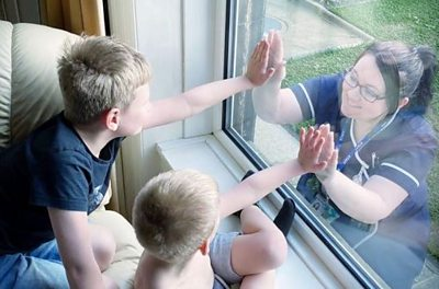 Care nurse touches palms with children separated by window
