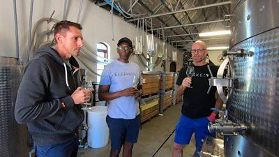 Three men in a winery sampling their wine