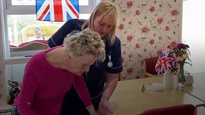 A carer helping a care home resident