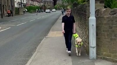 Louis walking down street with guide dog