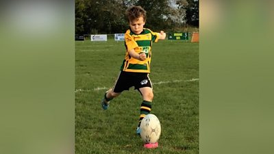 Seven-year-old Oscar kicking rugby ball