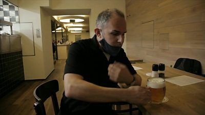Rob Cameron lowers his mask to sip beer at a brewery in Prague