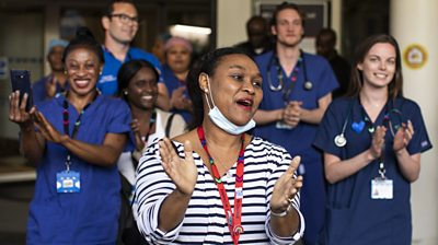 healthcare workers applaud outside a hospital in London