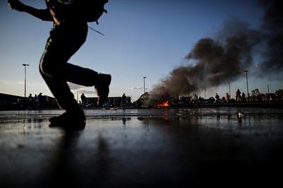 Man running past burning car