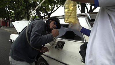 A man siphons fuel into a car