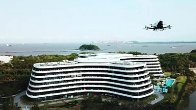 An automated aerial passenger vehicle flies towards a hotel