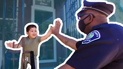 A police officer high fives a young child