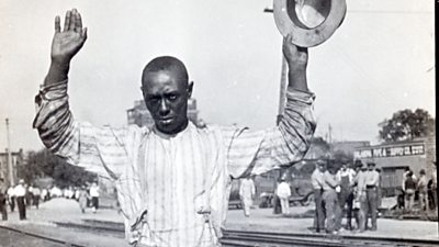 A black man holds his hands up