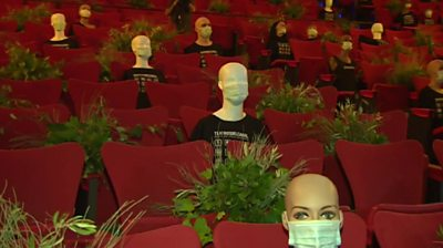 Dummies in masks in a theatre